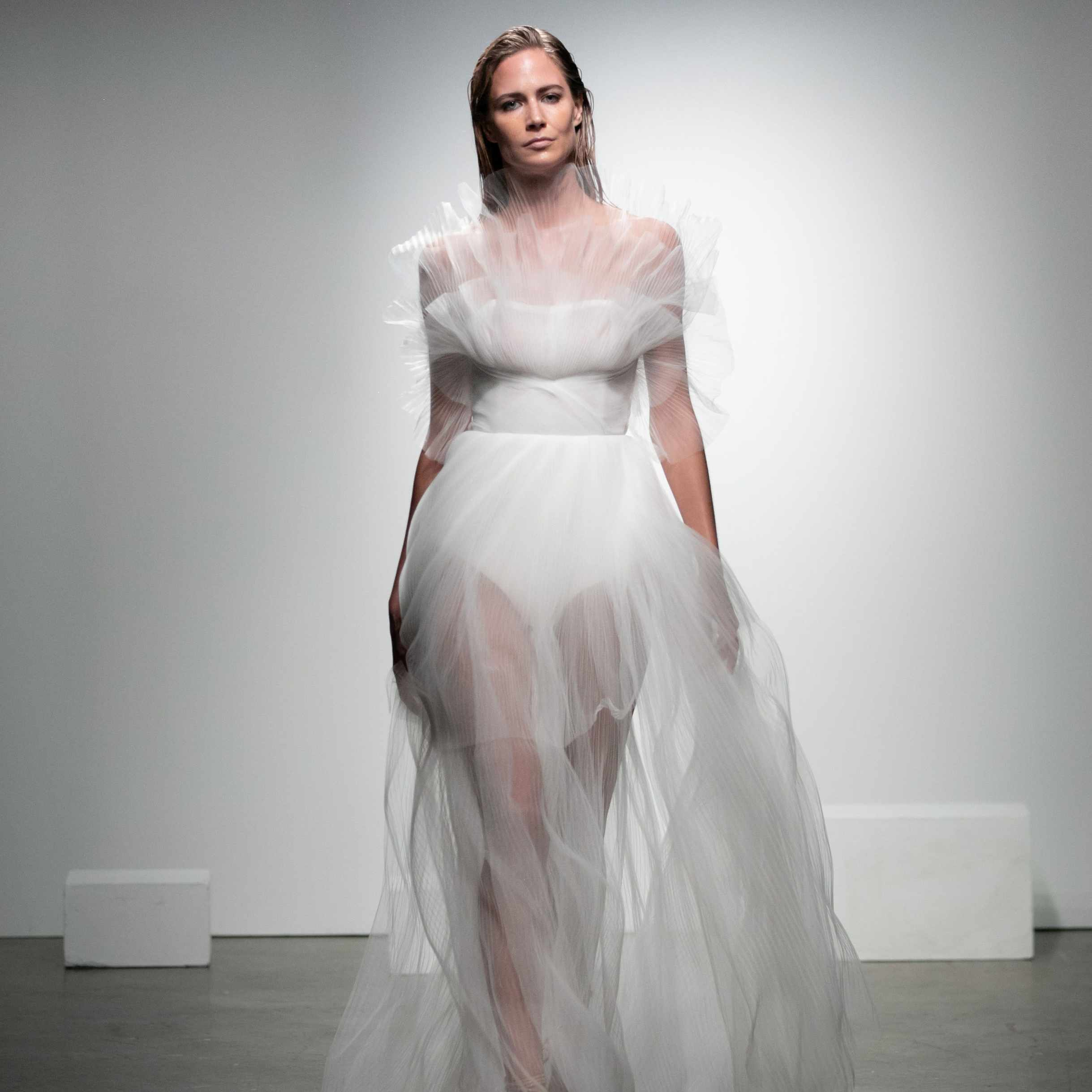 Model in bustier dress with see-through pleated tulle