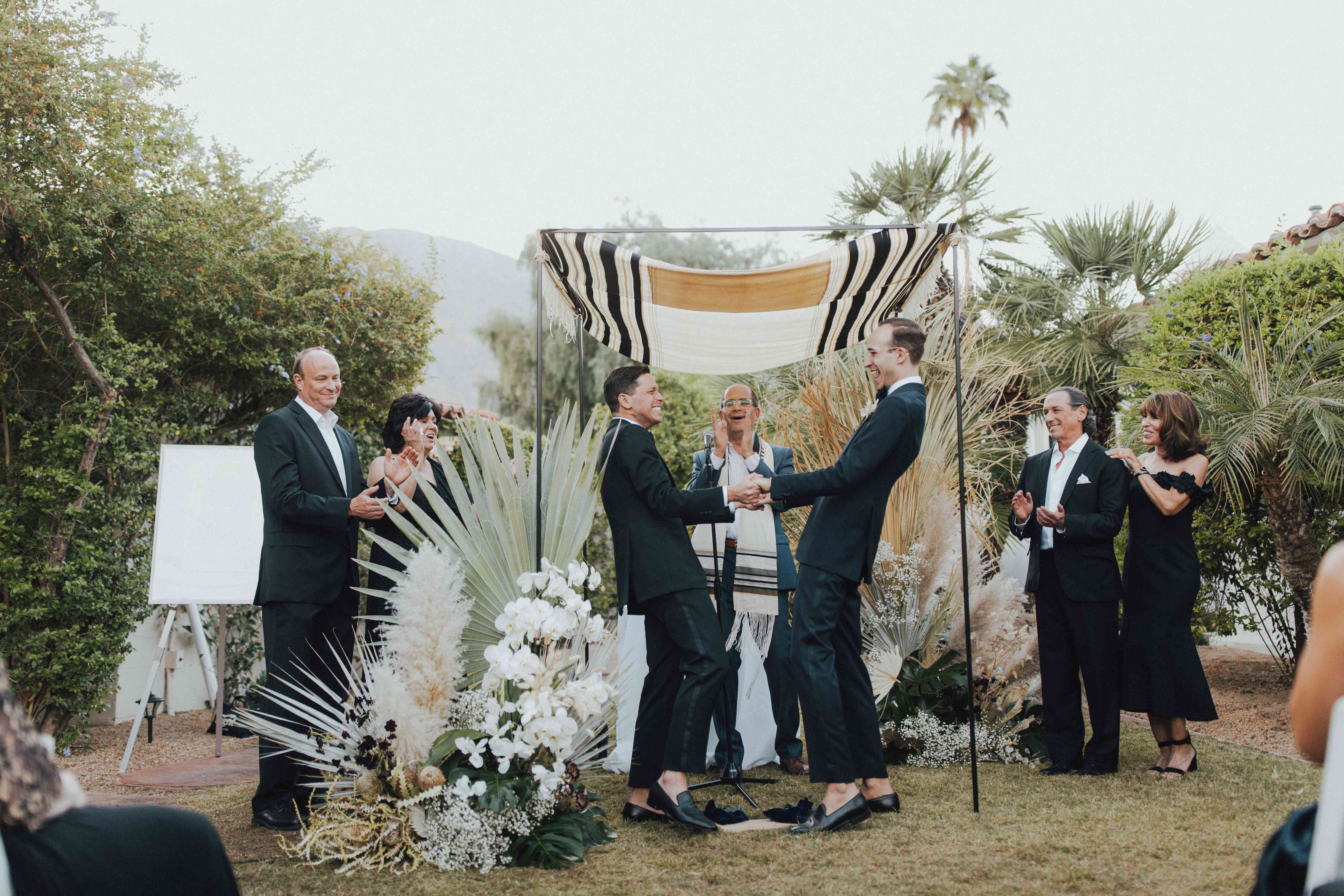 Grooms holding hands at the altar smiling