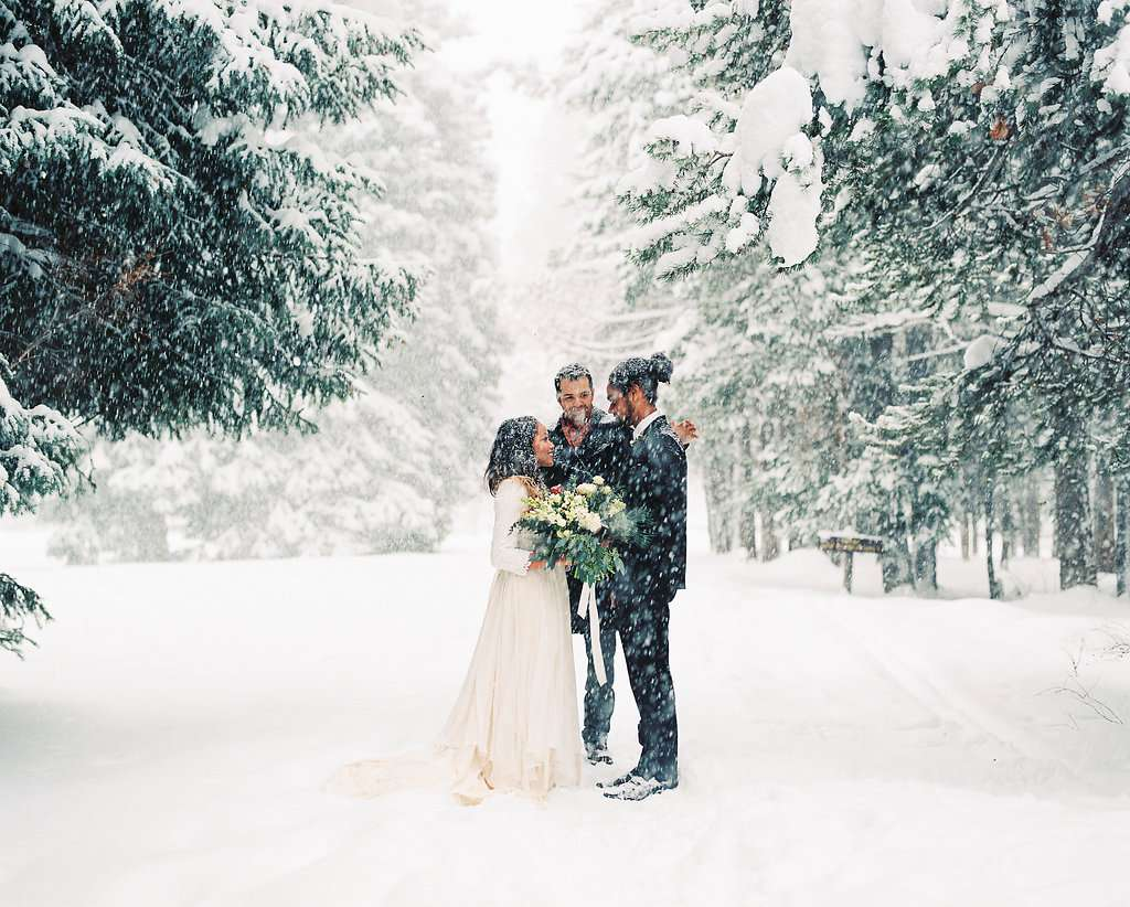 Bride and groom exchanging vows in the snow outside