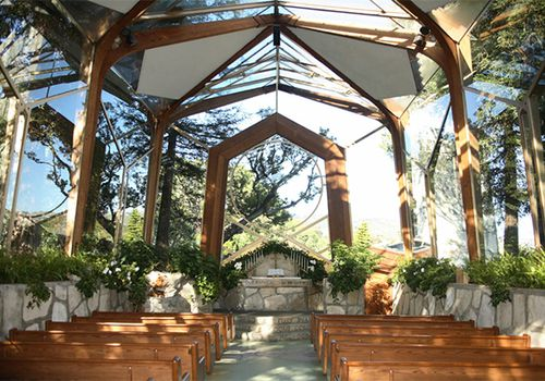 Wedding chapel with transparent ceiling, wooden benches and greenery