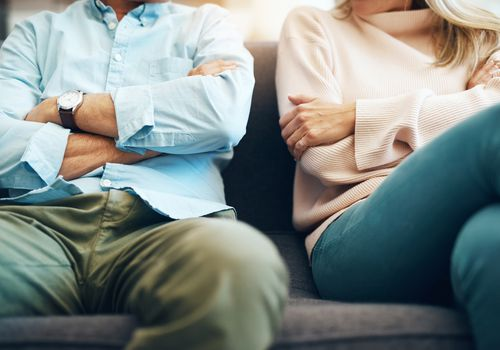Couple sitting on couch with crossed arms