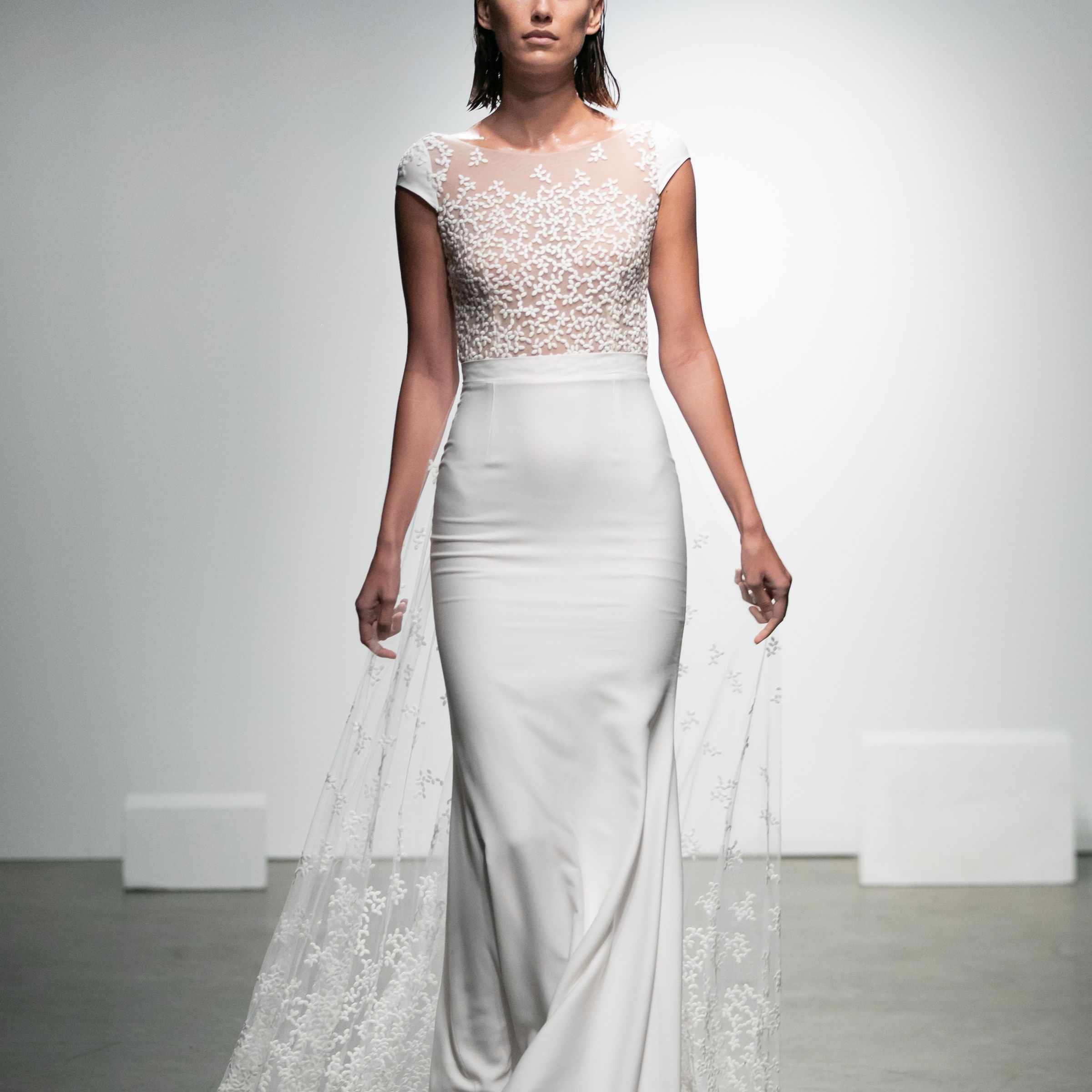 Model in high-neck crepe dress with cap sleeves and floral-embroidered tulle with a train