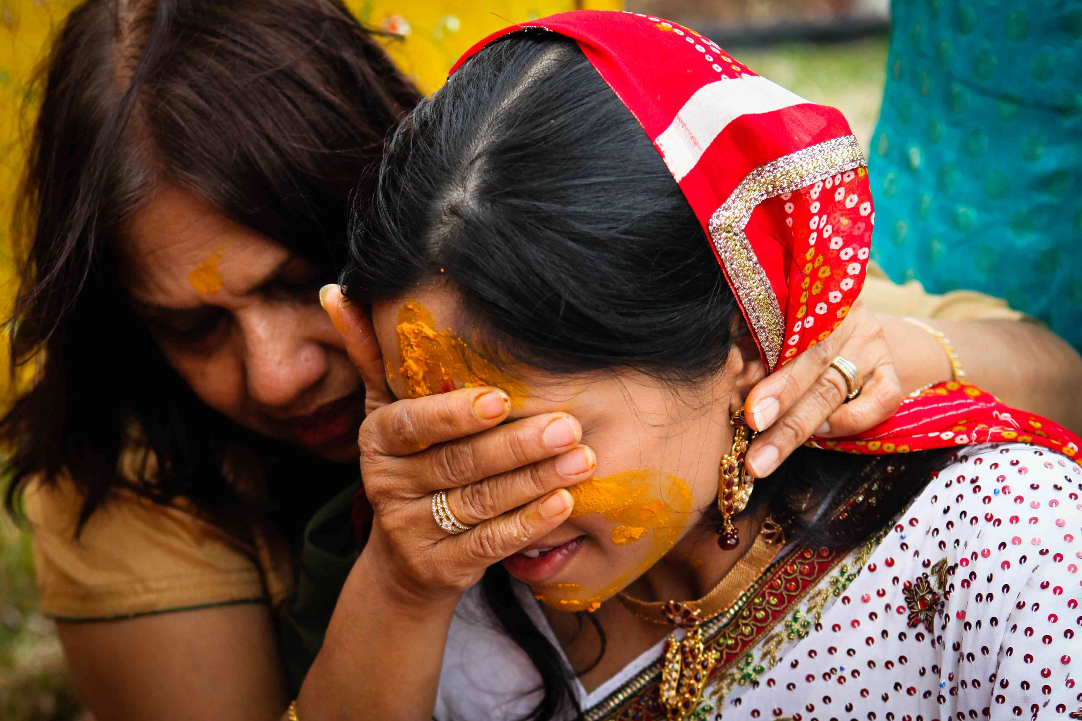 Woman massaging engaged Indian woman's face with turmeric paste during Haladi ceremony