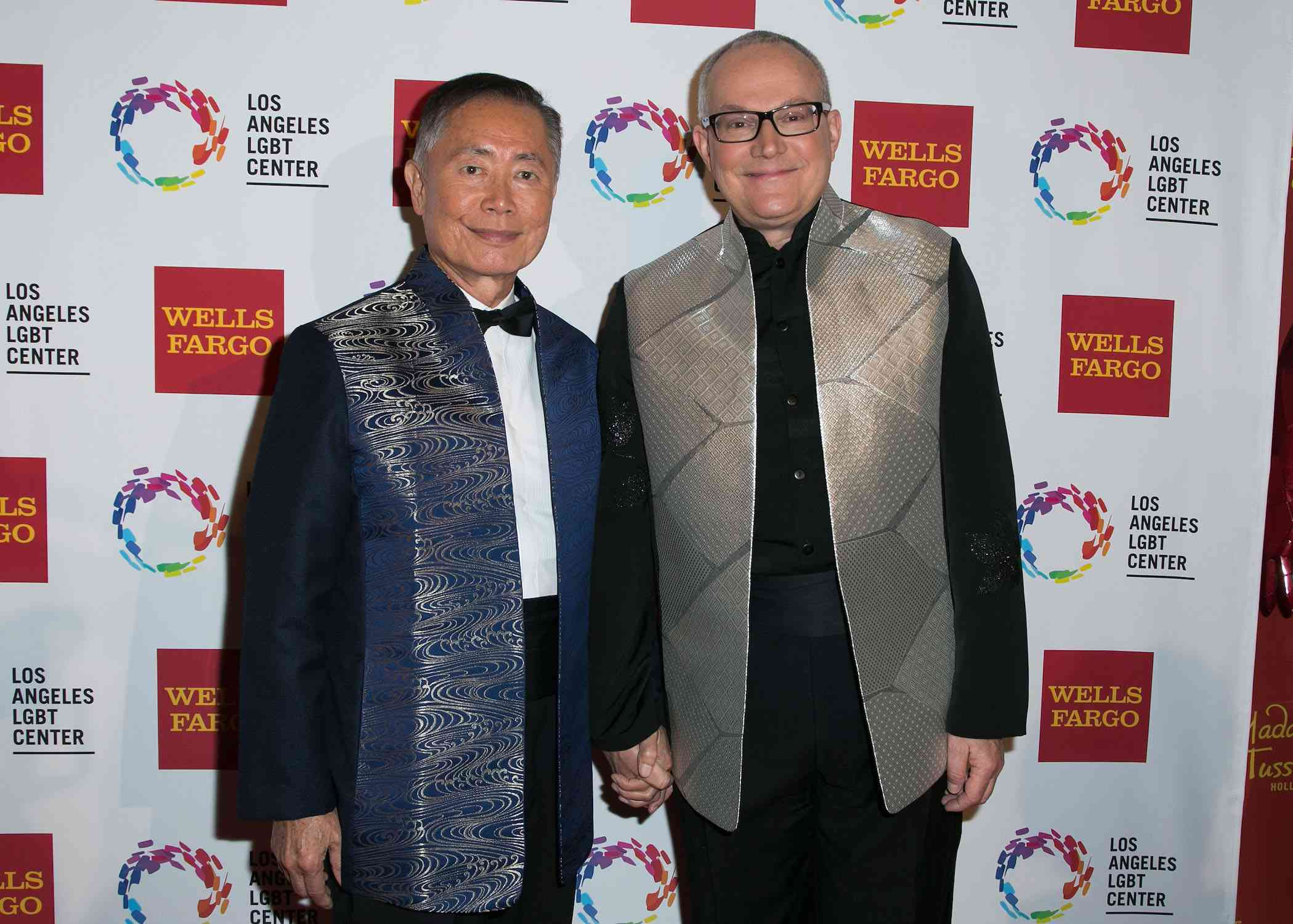 George Takei holds husband Brad Takei's hand in matching printed suit jackets