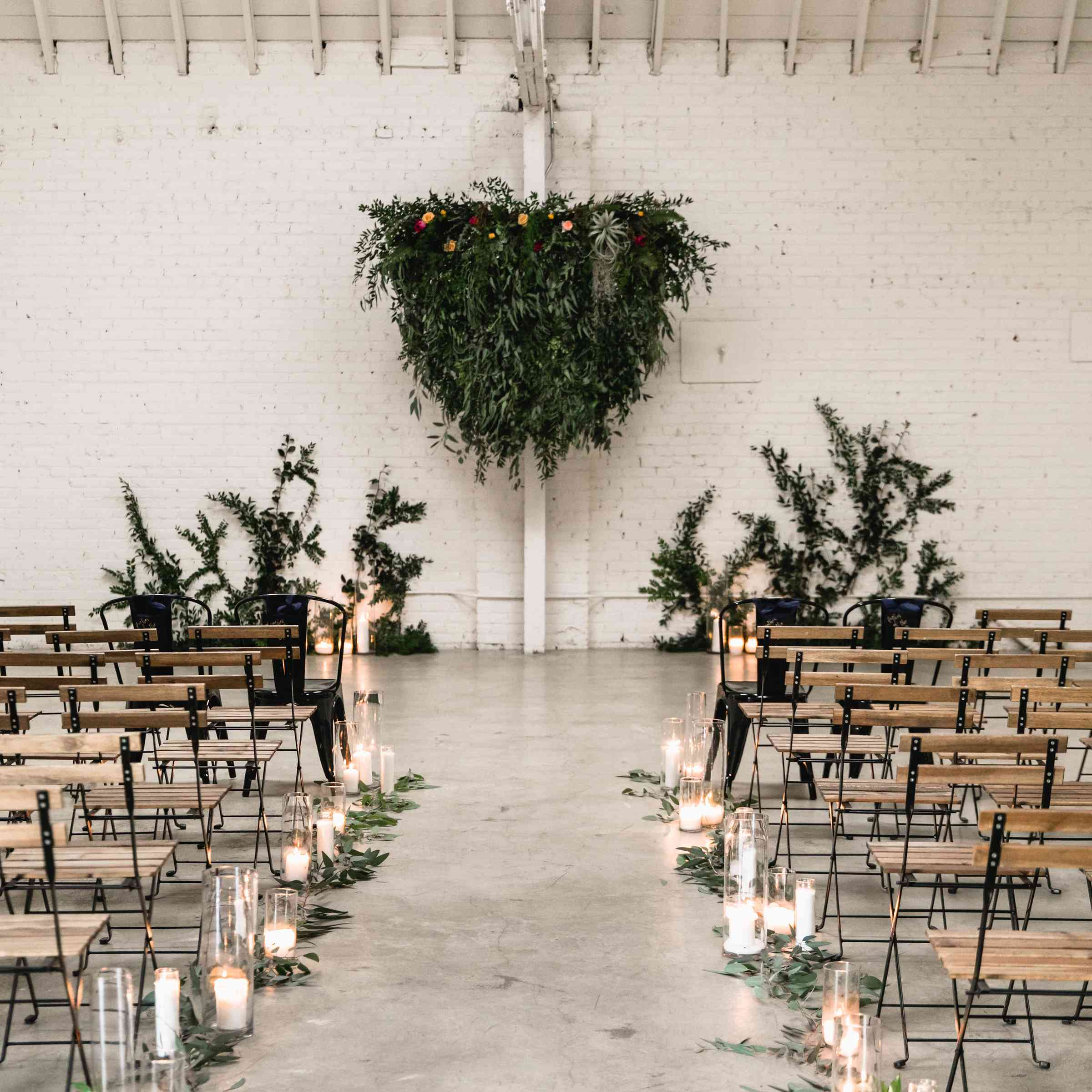 Ceremony aisle on concrete floor decorated in foliage and candles