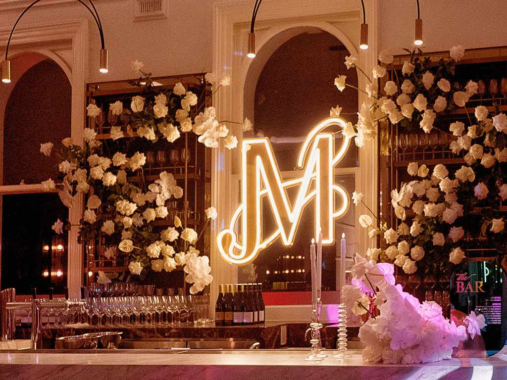 bar with roses and large neon monogram