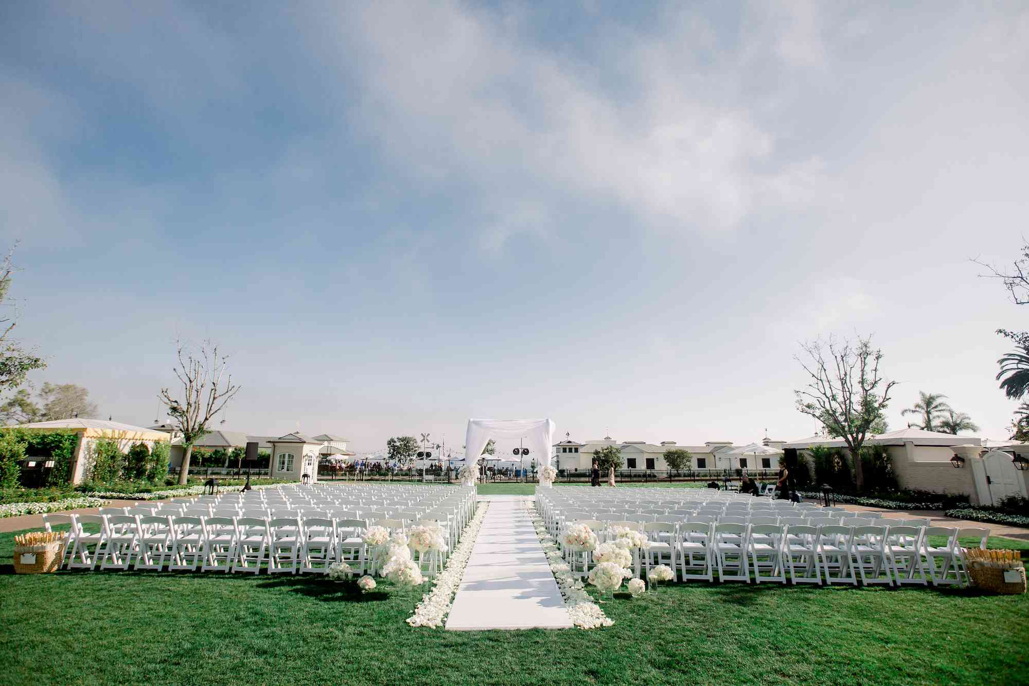 Backyard ceremony with white runner, white petals lining the aisle, and varying heights of glass vases filled with white flowers at the start