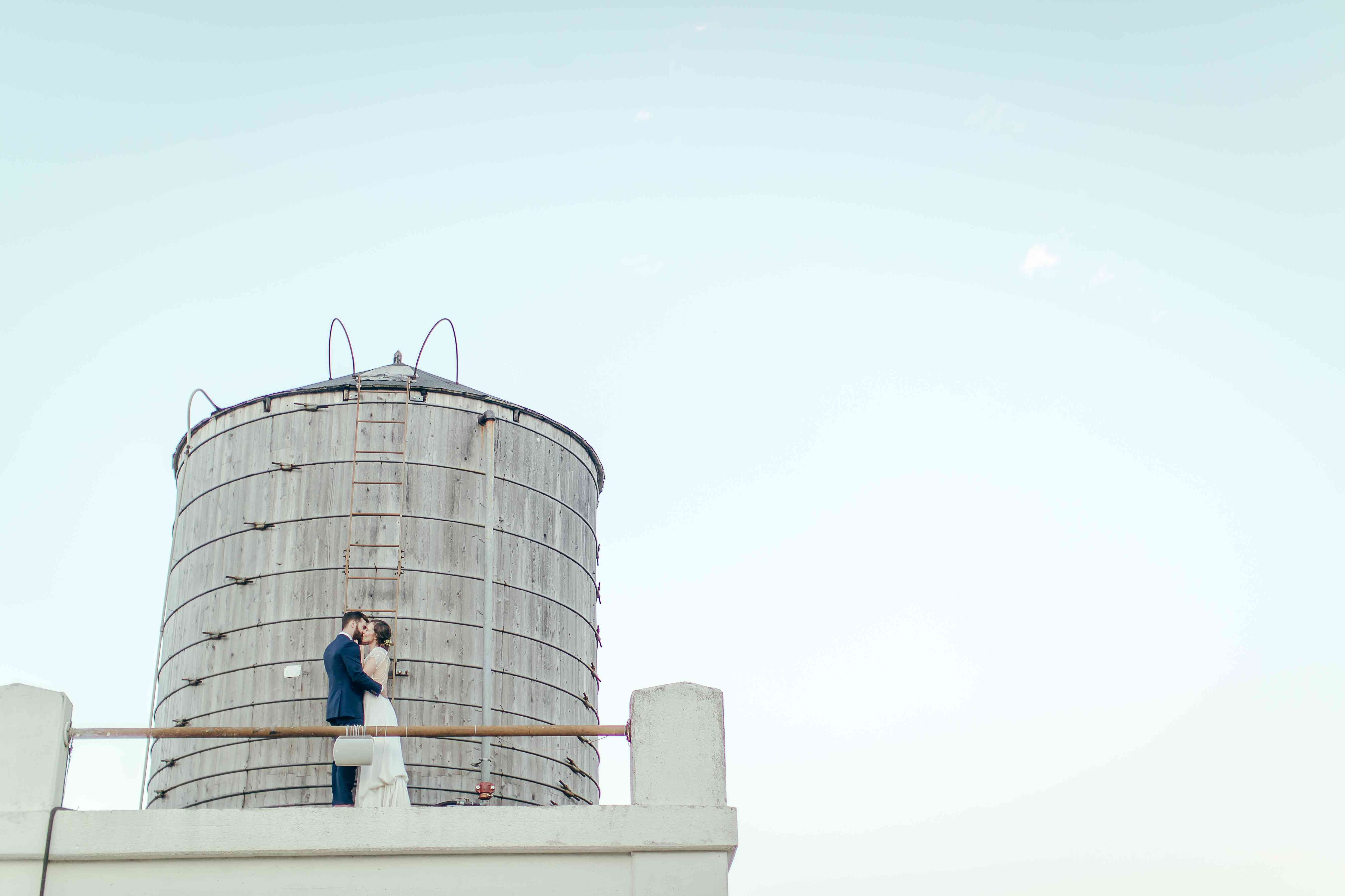 Bride and groom kissing near water tower