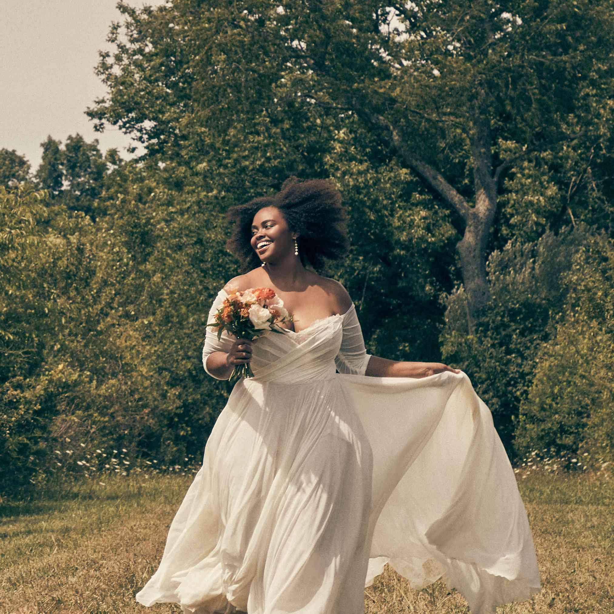 Woman walking through grass in off-the-shoulder tulle wedding gown