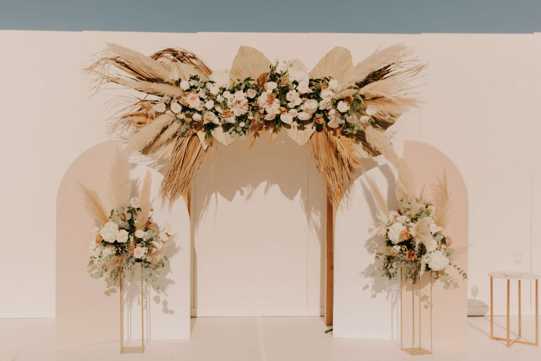 Wedding arch decorated with white, pink and gold flowers, dried palm leaves, and pampas grass