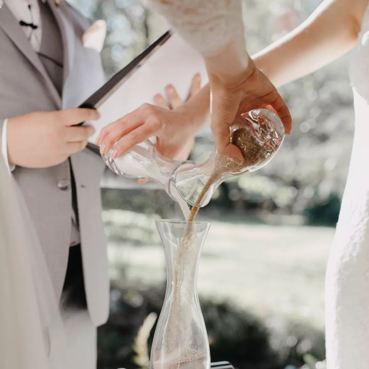 Bride and groom pouring sand into vessel