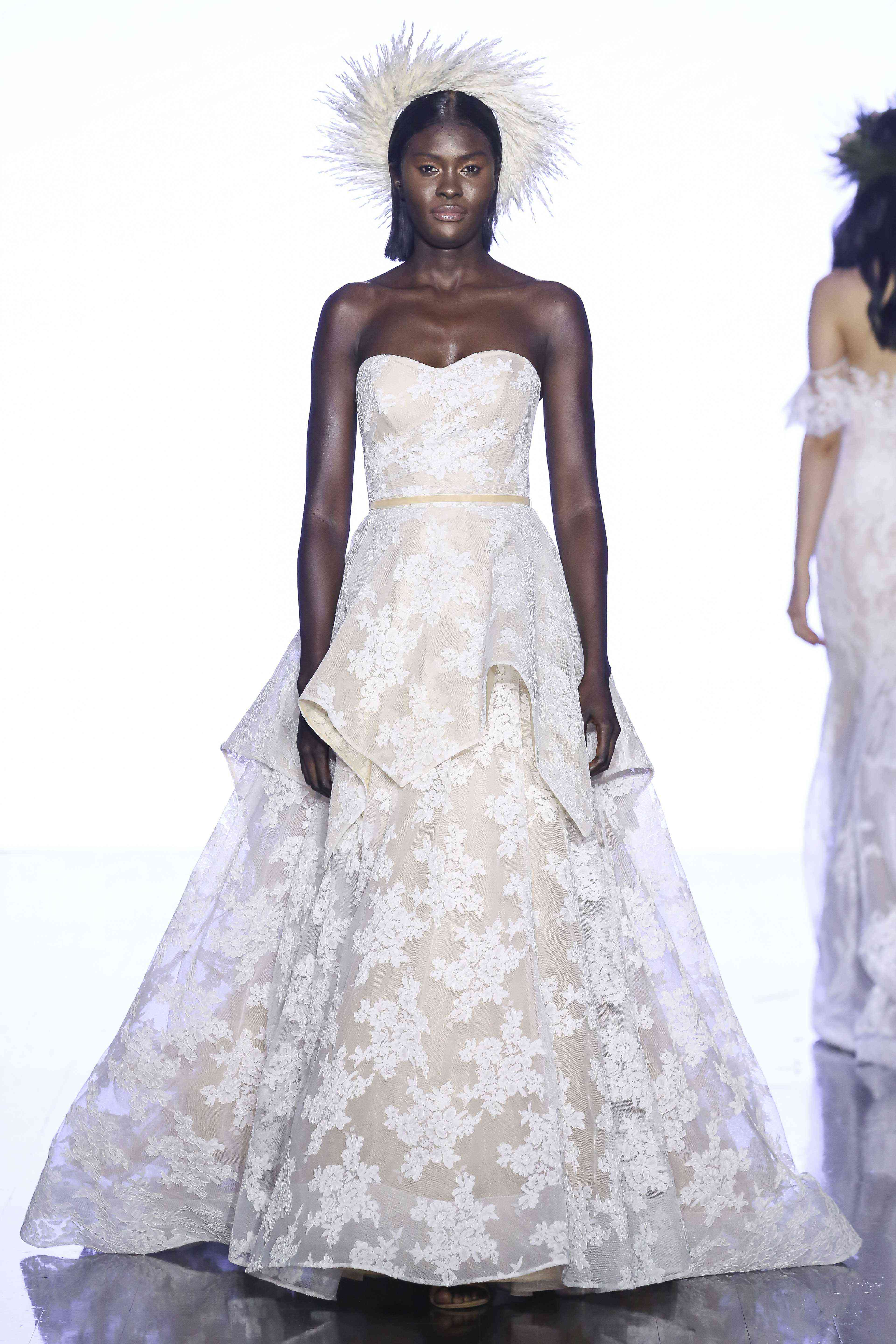 Model in strapless lace and organza ballgown with a tiered skirt