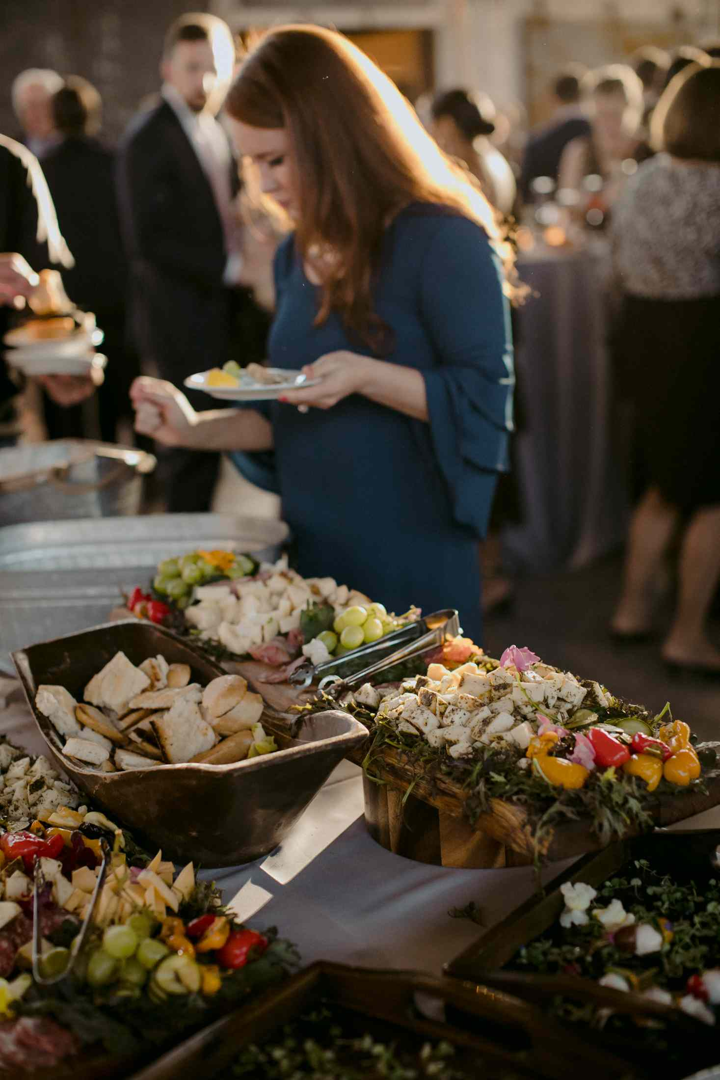 Woman making a plate at a fruit and cheese buffet