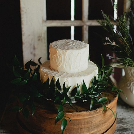 A simple two-tiered white wedding cake on an ivy-covered wooden cake stand