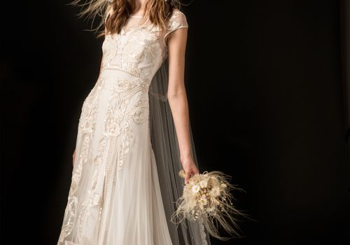 Model in long-sleeve embroidered ruffle wedding dress