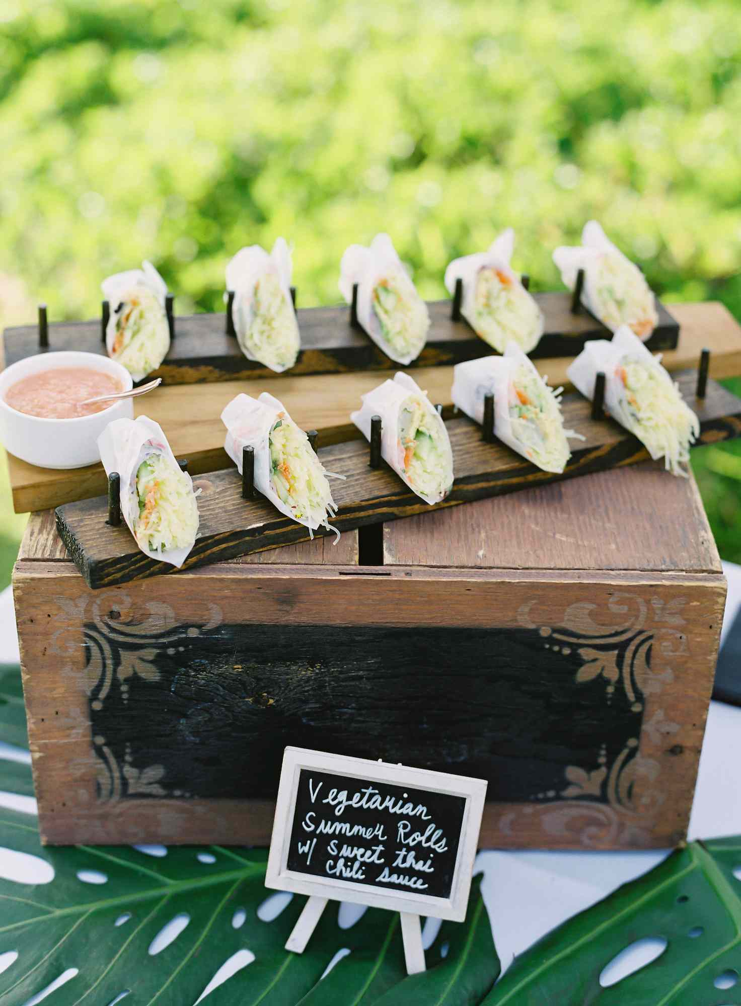 Wood box with vegetarian summer rolls and a sauce