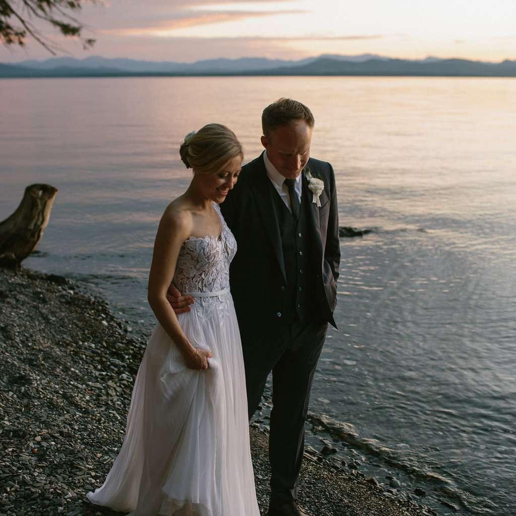 Bride and groom walking along beach