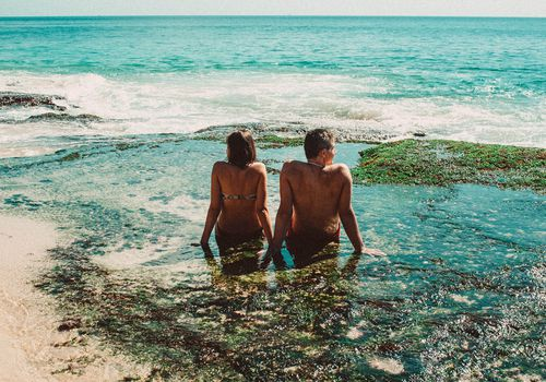 couple sitting on beach looking in different directions