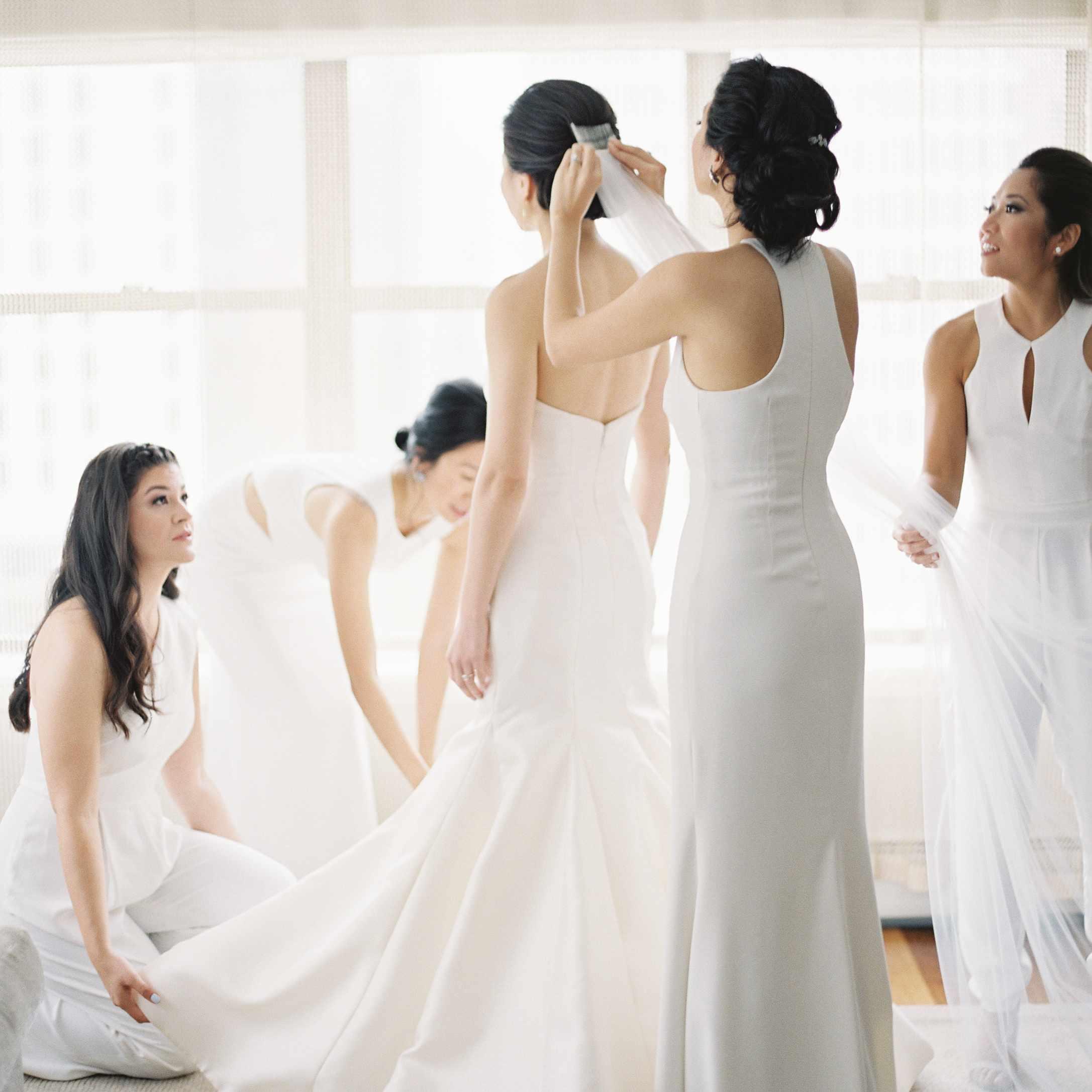 Bridesmaid helping bride dress
