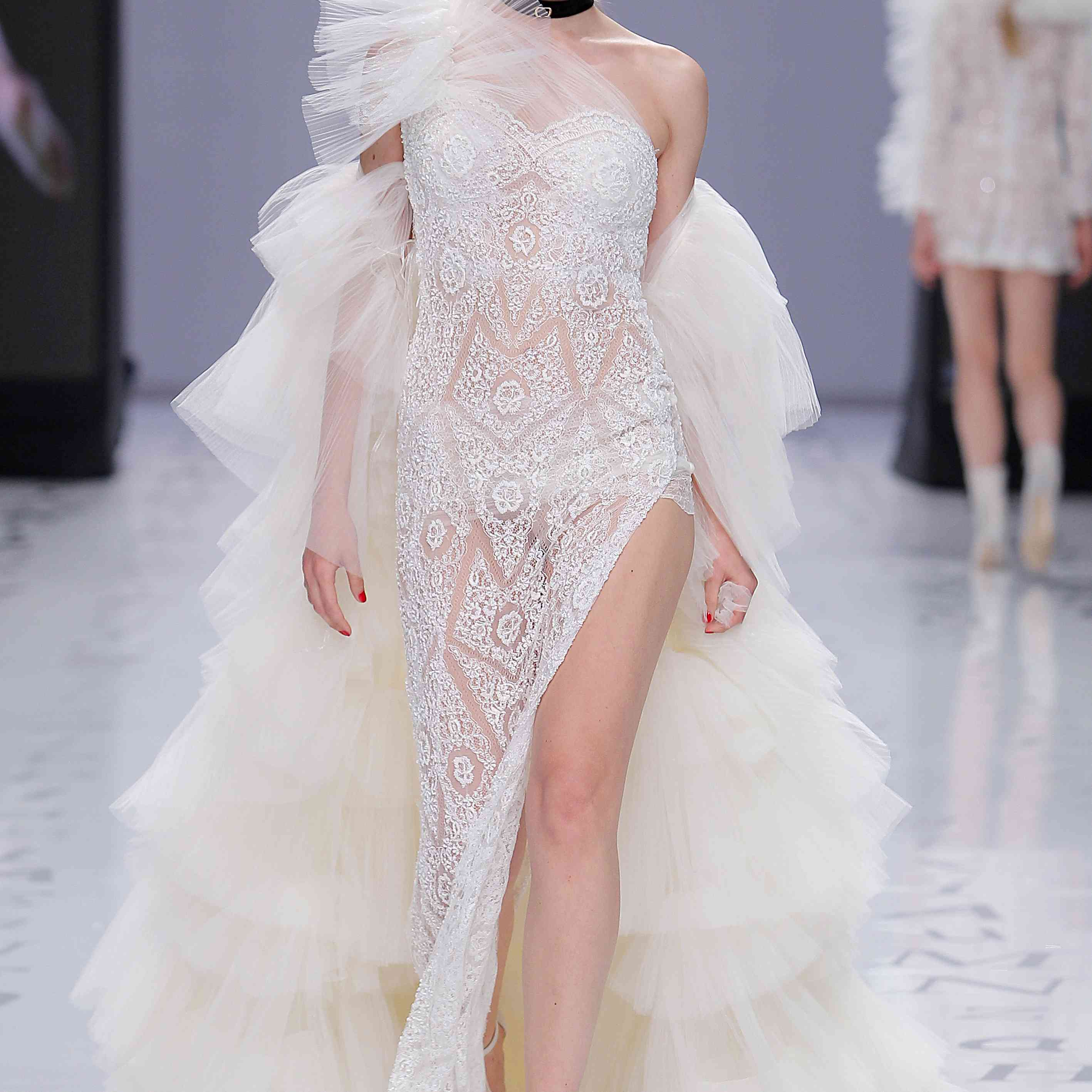 Model in a strapless rhinestone-embroidered tulle mermaid dress with a deep side slit and a one-shouldered tulle overlay with a dramatic shoulder embellishment and an off-the-shoulder tiered tulle coat