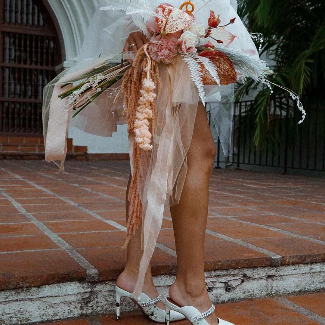 Bride holding a peach bouquet with unique flowers