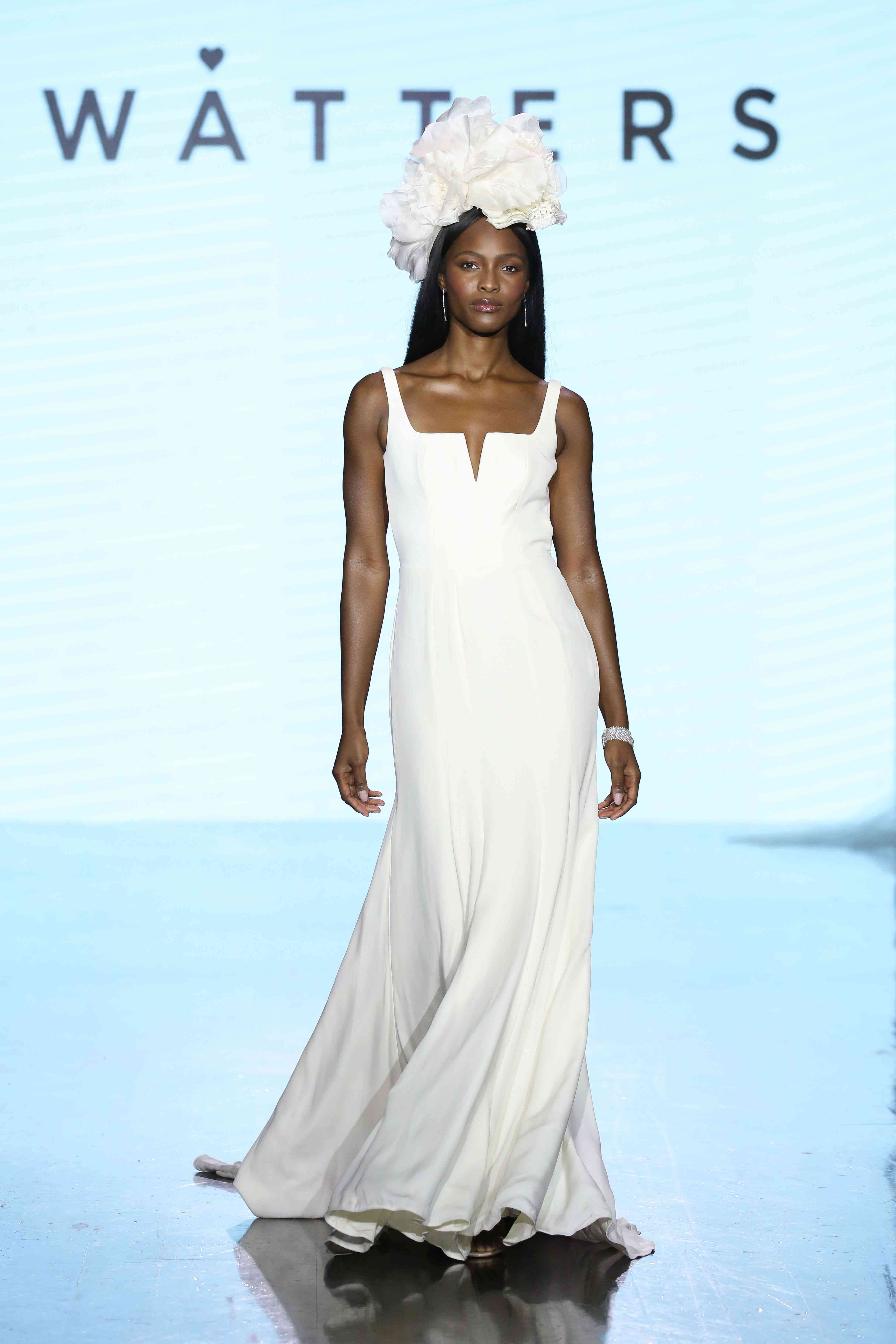 Model on runway in sleeveless wedding dress with notched square neckline
