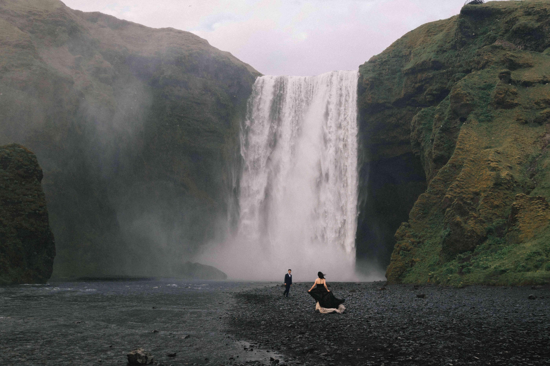 Couple at Reynisfjara Beach waterfall in Iceland