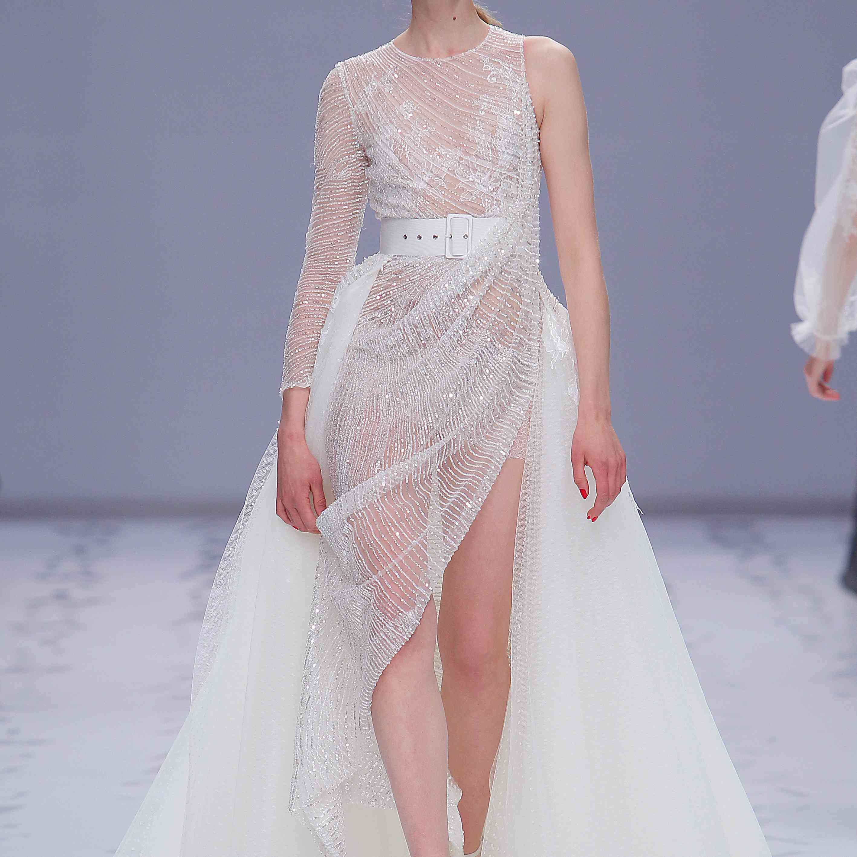 Model in a delicate sheer dress with lace and sequins, an asymmetrical sleeve, an asymmetrically draped skirt, and a plumetti overskirt with a train