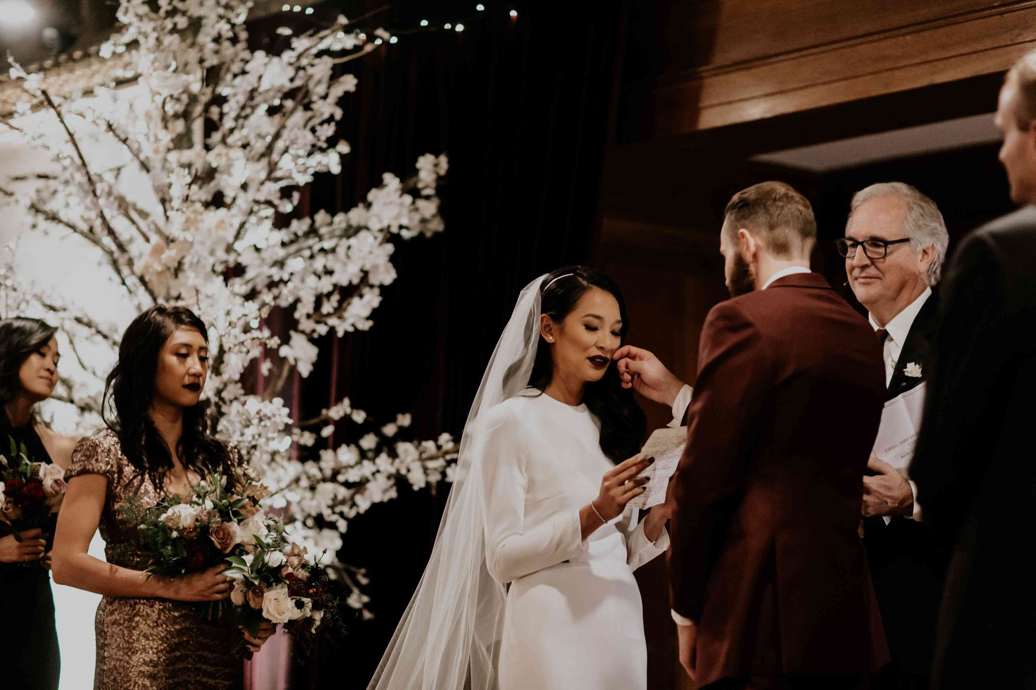 Groom wipes away bride's tear while she reads wedding vows
