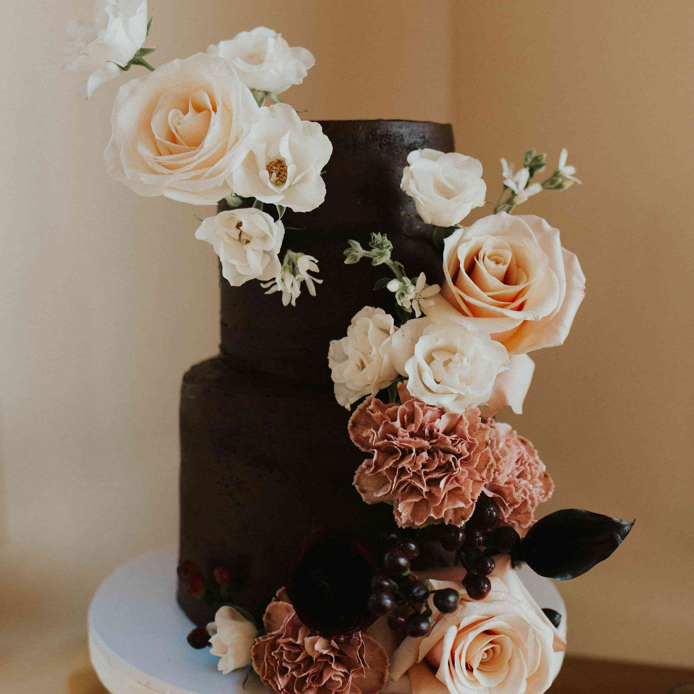 Black tiered wedding cake with blush, red, and cream floral accents