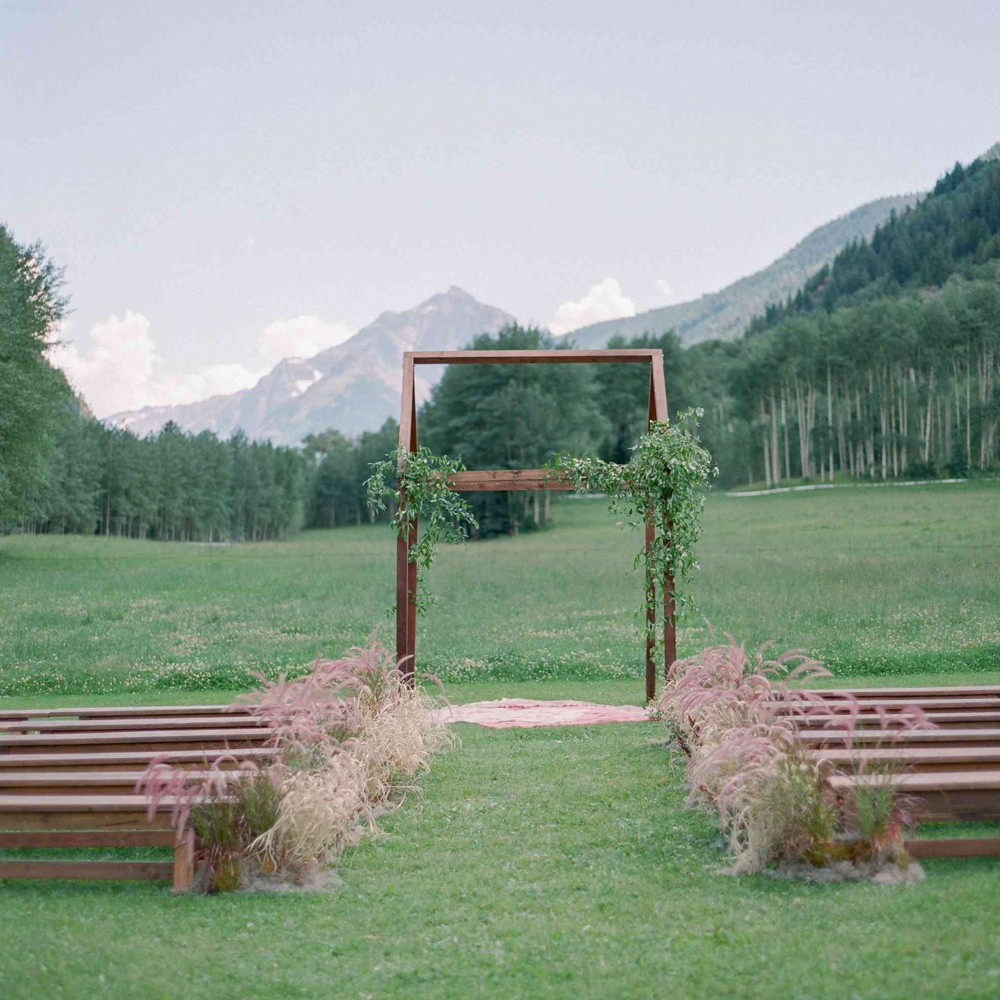 Ceremony site with mountain views on grass with brown grasses lining aisle