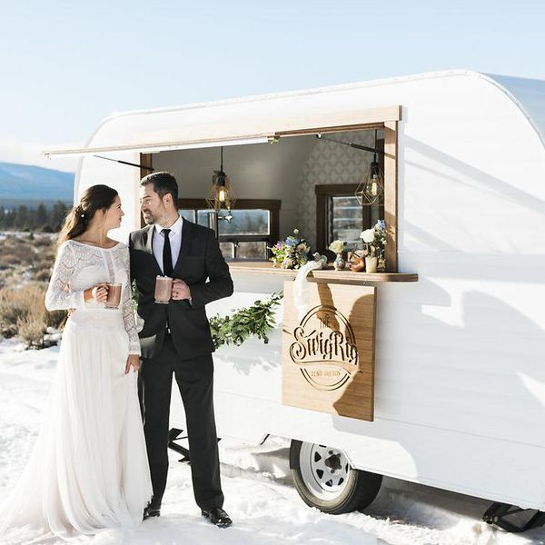Winter wedding on a mountain, bride in long sleeves, in front of mobile bar trailer, outdoor reception, cheers