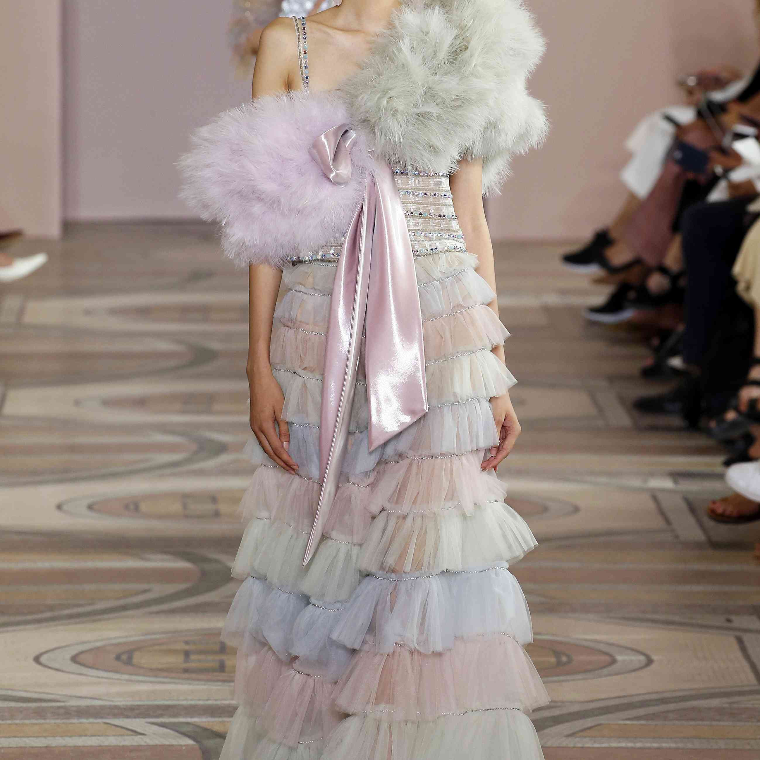 A model walks the runway in multicolored tulle wedding dress with fur