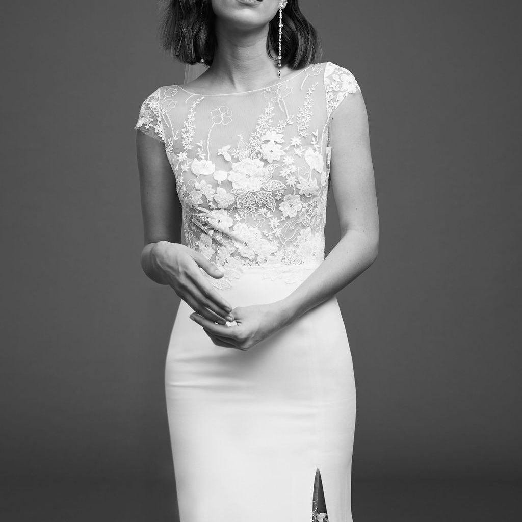 Model in short-sleeve dress with floral embroidered bodice, short sleeves, and side slit on the skirt