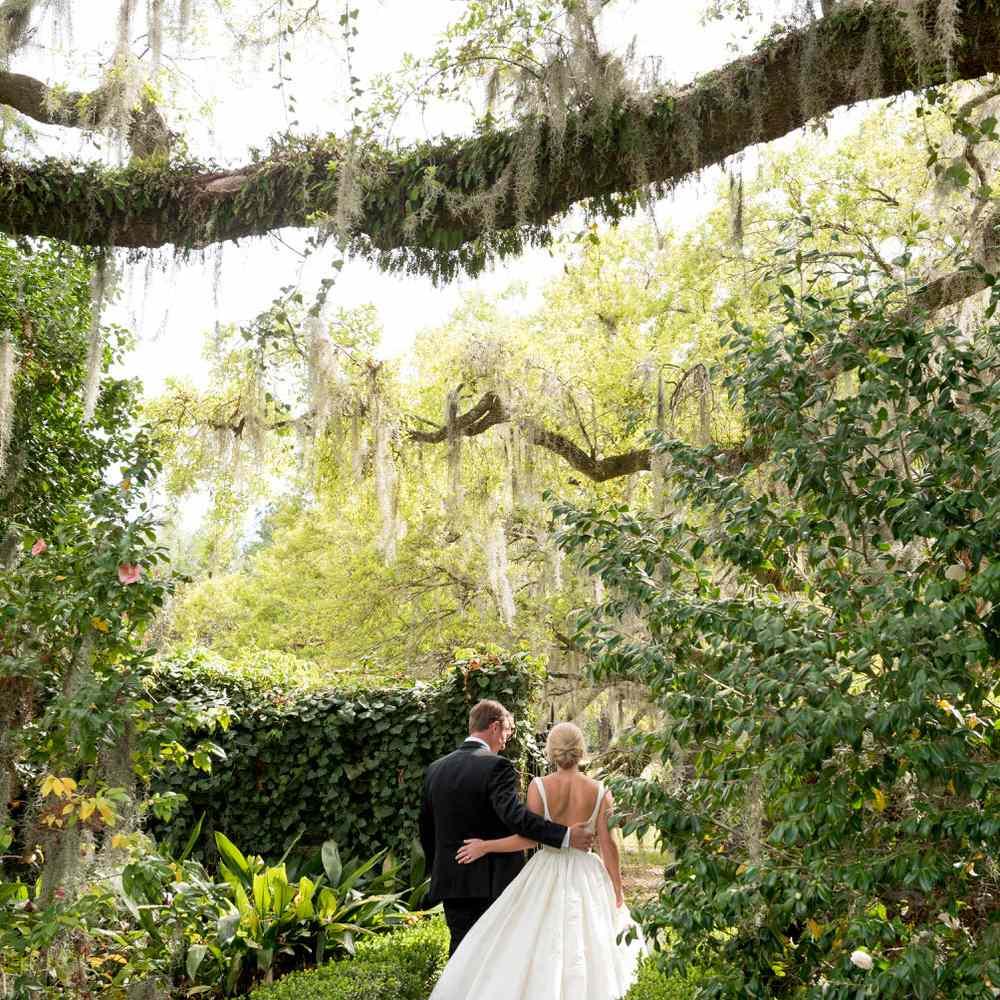 <p>A couple walks through lush gardens.</p>