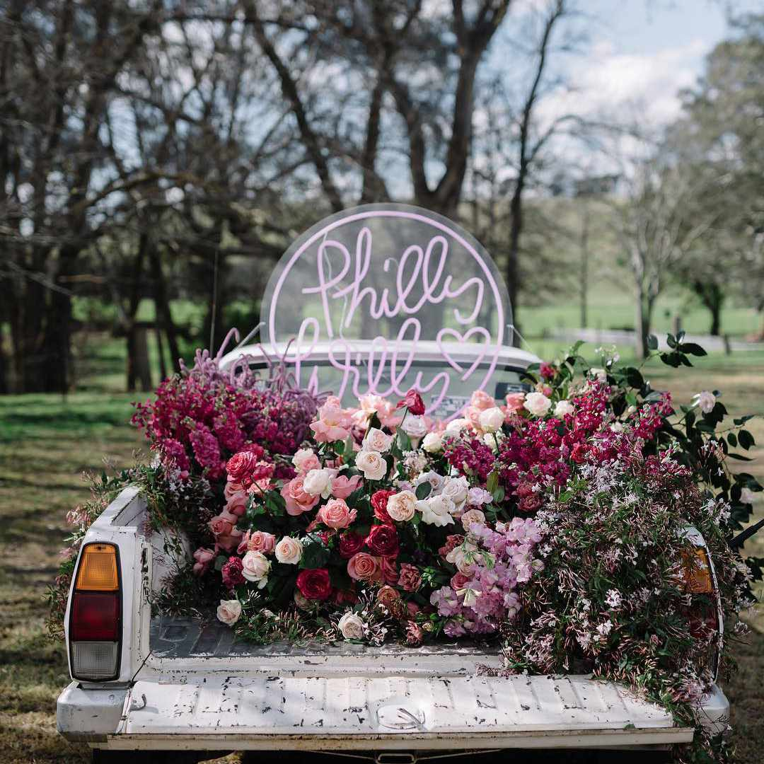 Pickup truck with bouquets of pinks flowers and a neon sign in the truckbed