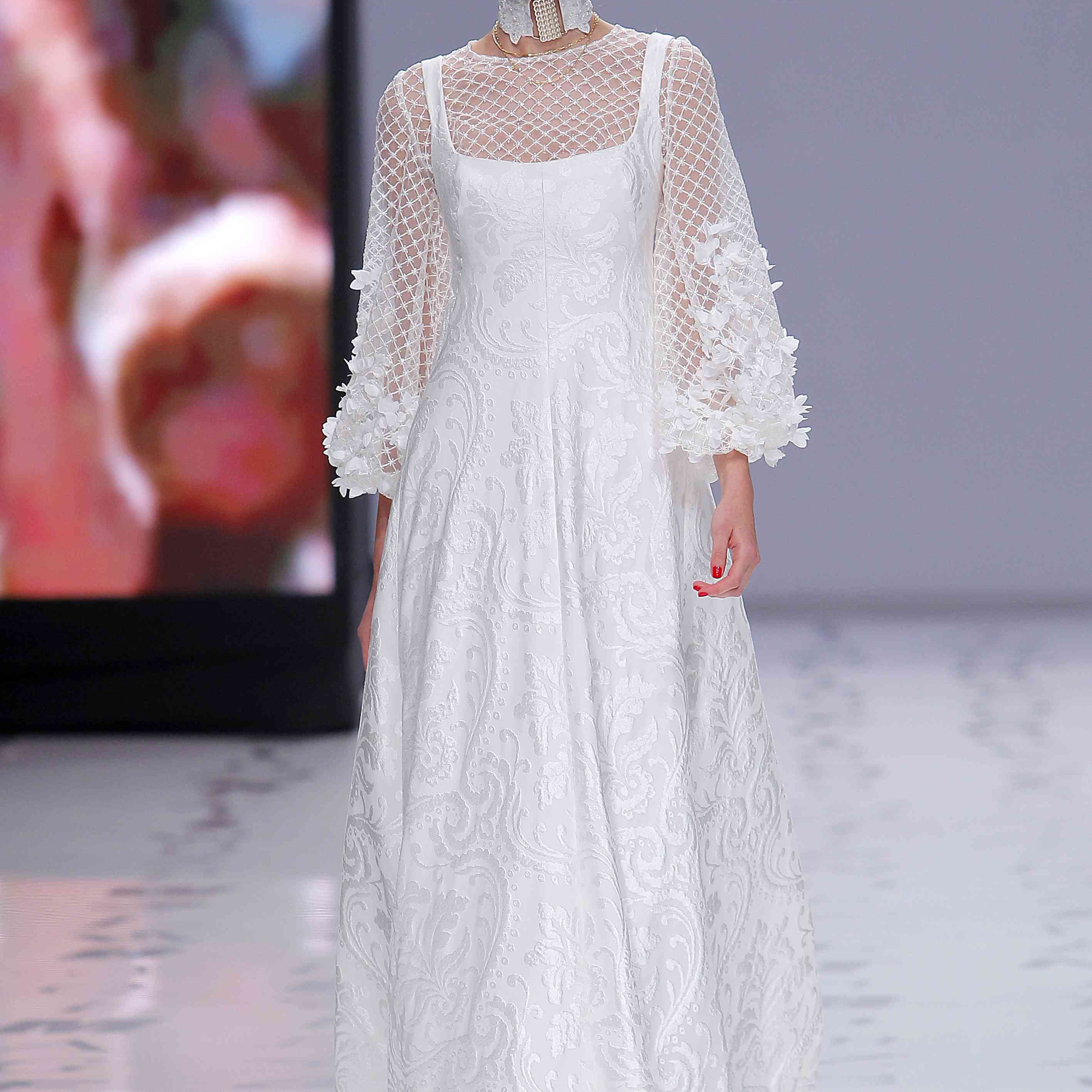 Model in white-on-white damask A-line gown with embroidered tulle puff sleeves decorated with hand-sewn 3D georgette flowers