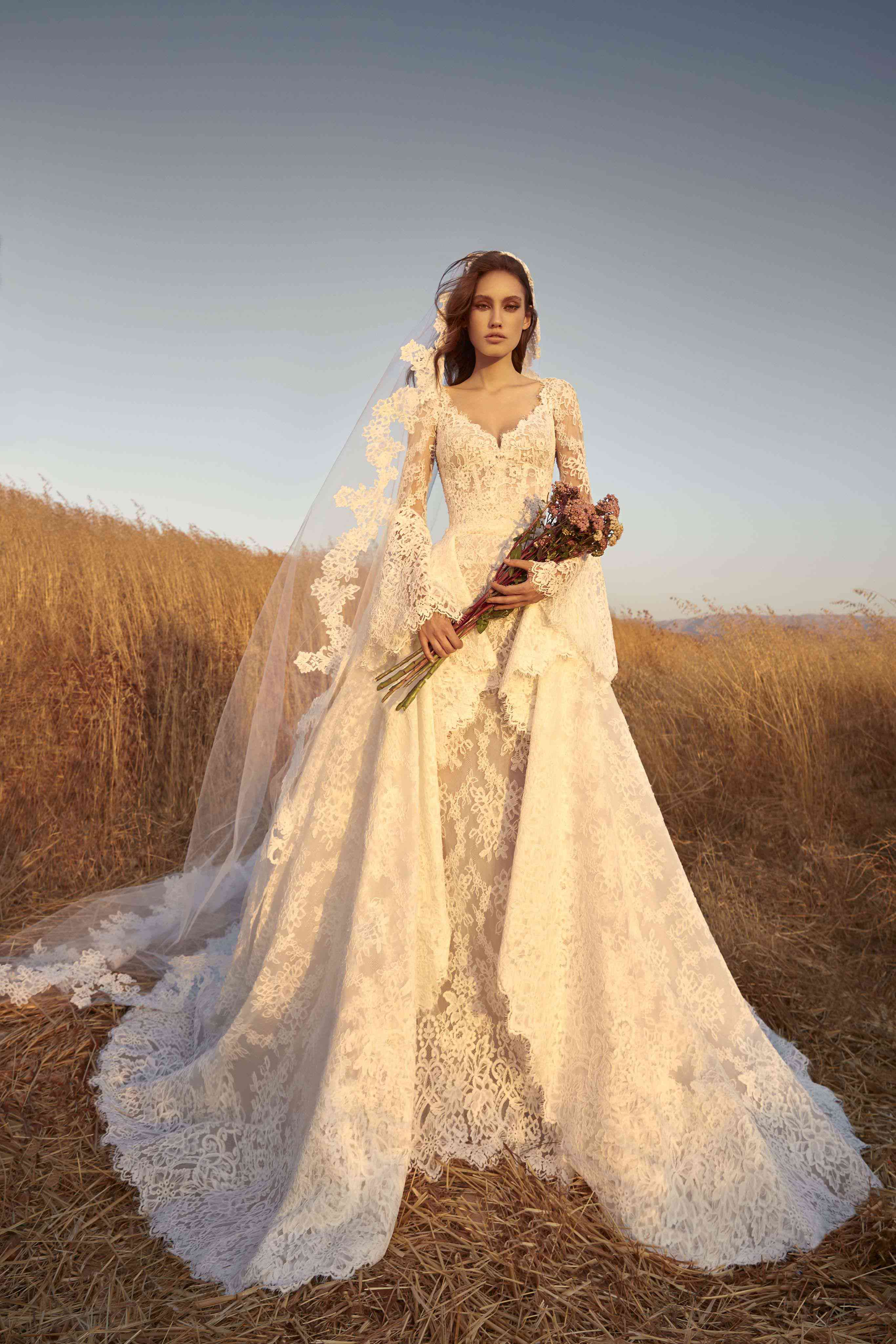 Model in long-sleeve allover lace dress with bell sleeves and a dramatic lace overskirt with a matching veil