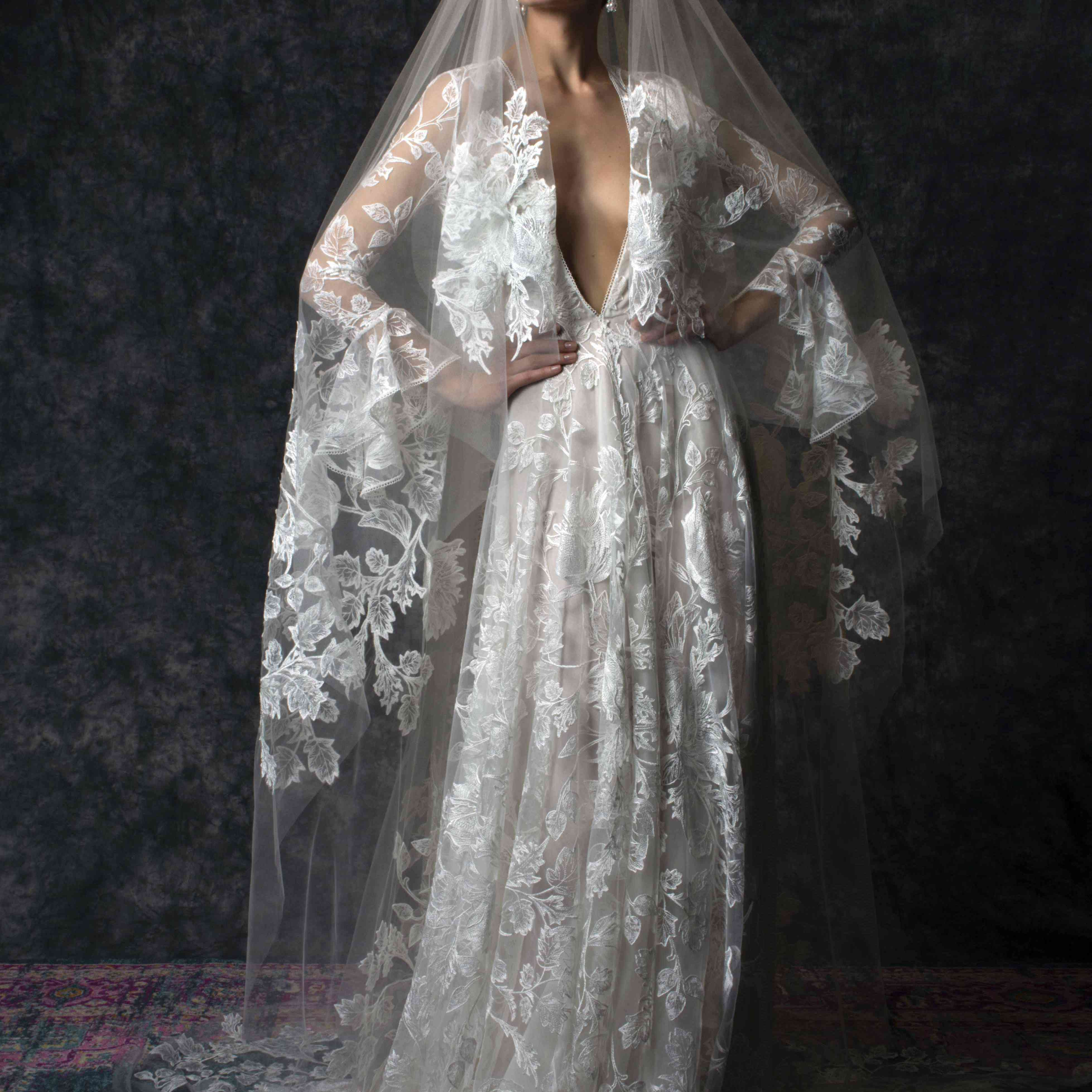 Model in long-sleeve lace gown with plunging neckline