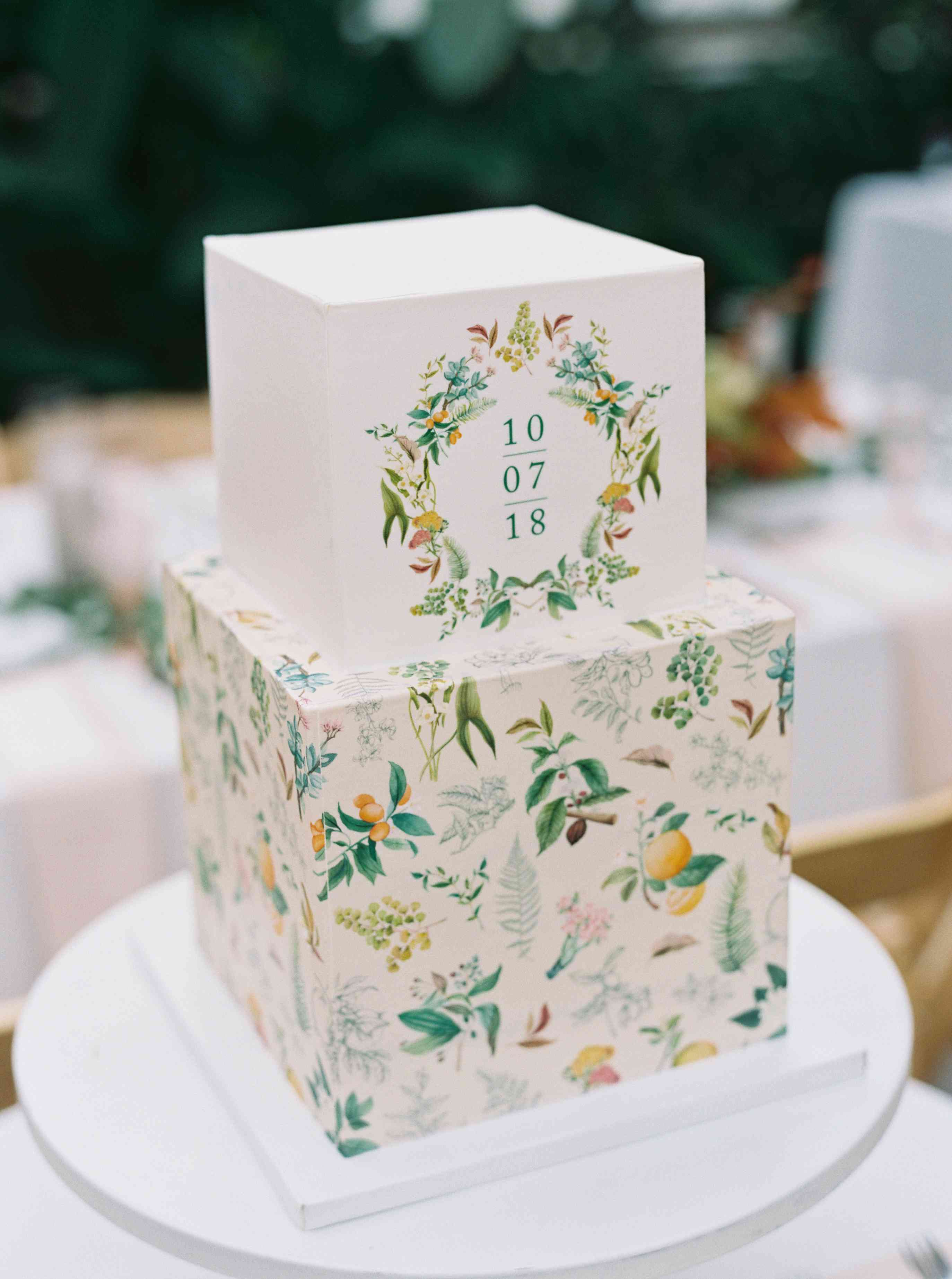 Two-tiered square wedding cake with floral print and the wedding date printed on the top tier