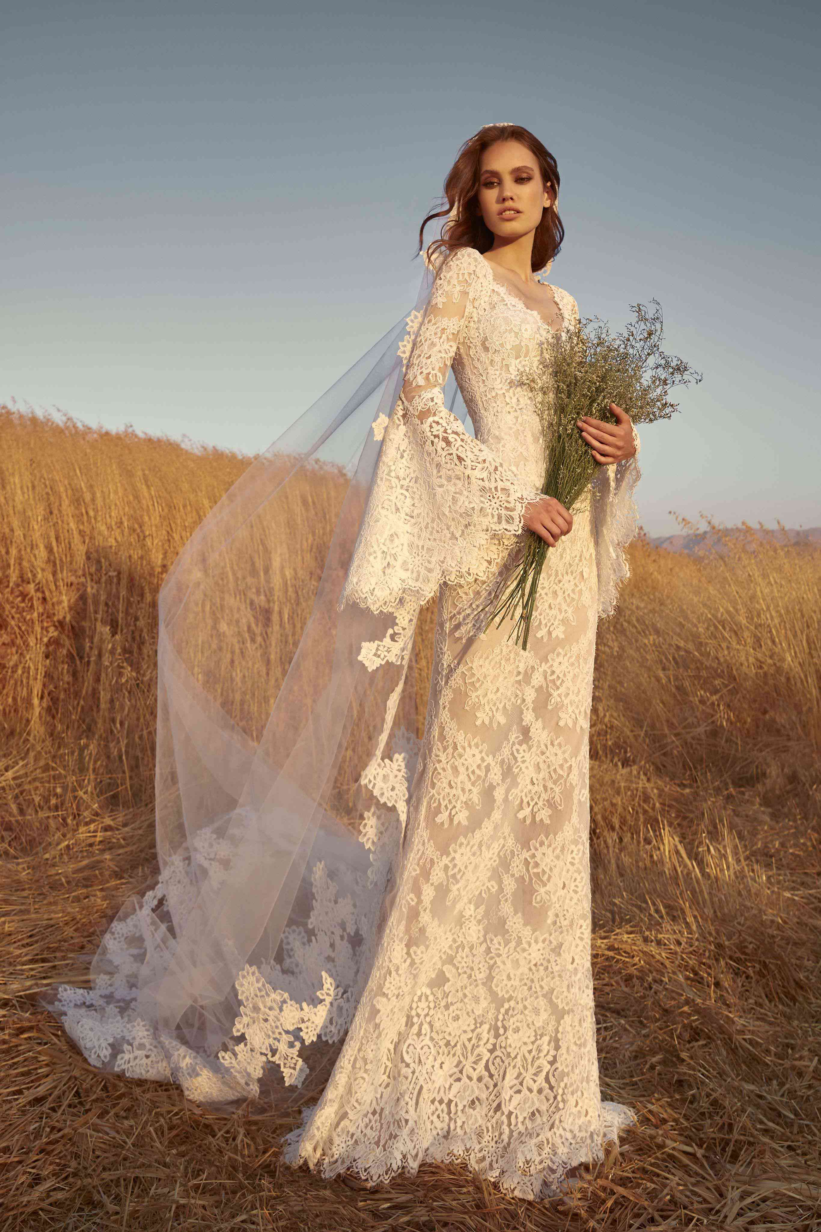 Model in an allover lace sheath gown with long bell sleeves