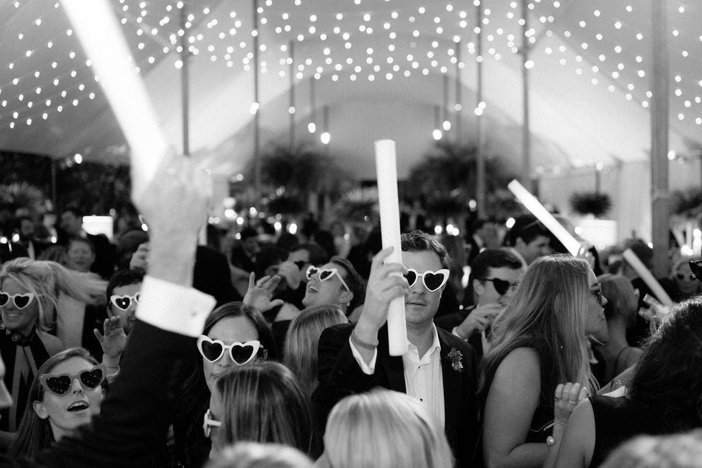 Wedding guests on the dancefloor wearing heart-shaped glasses