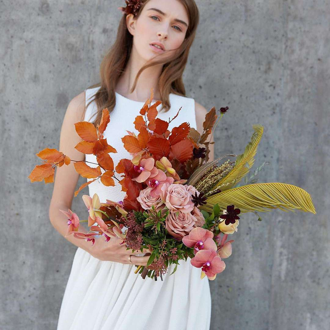 Bride holding bouquet of autumnal foliage branches, cappuccino roses, phalaenopsis orchids, chocolate cosmos, and dried sago palm leaves