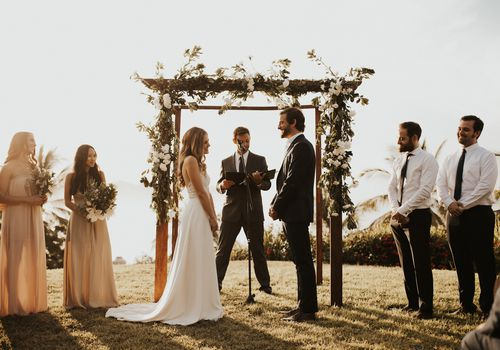 Bride and Groom in front of altar with wedding party and officiant reading in microphone