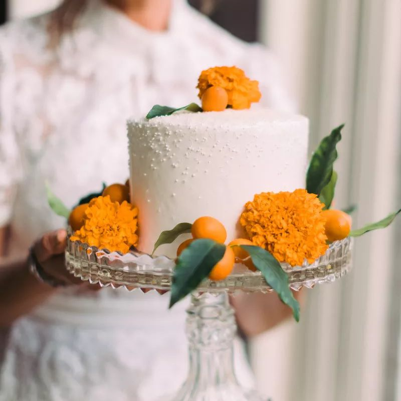 Small white wedding cake with marigold flowers