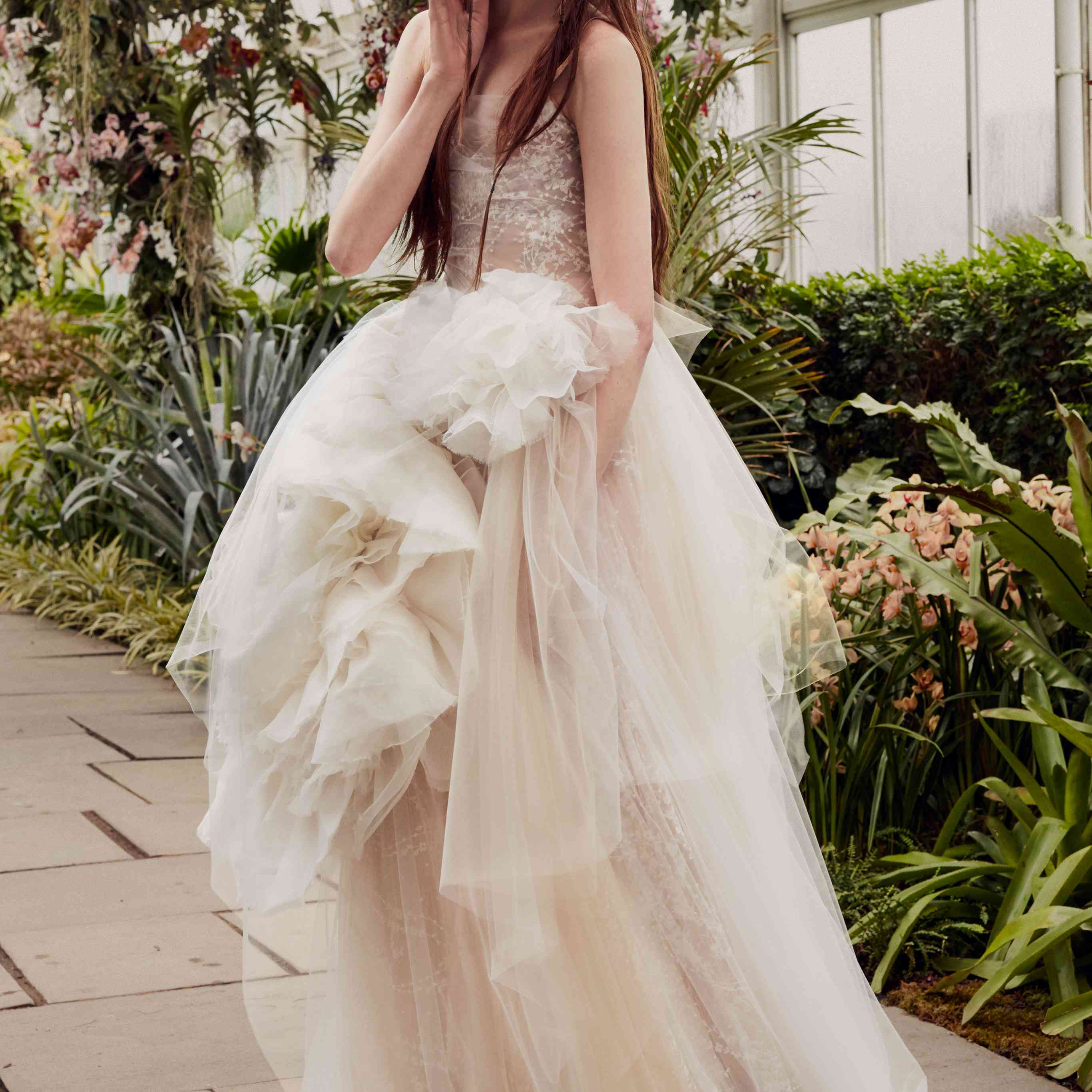 Model in a nude strapless embroidered tulle gown with a white flower under an asymmetrical draped skirt