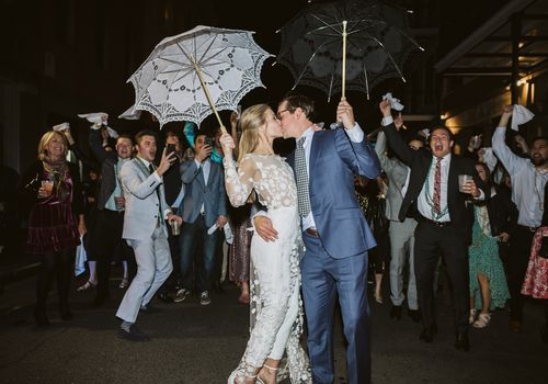 The couple kisses during the second line procession