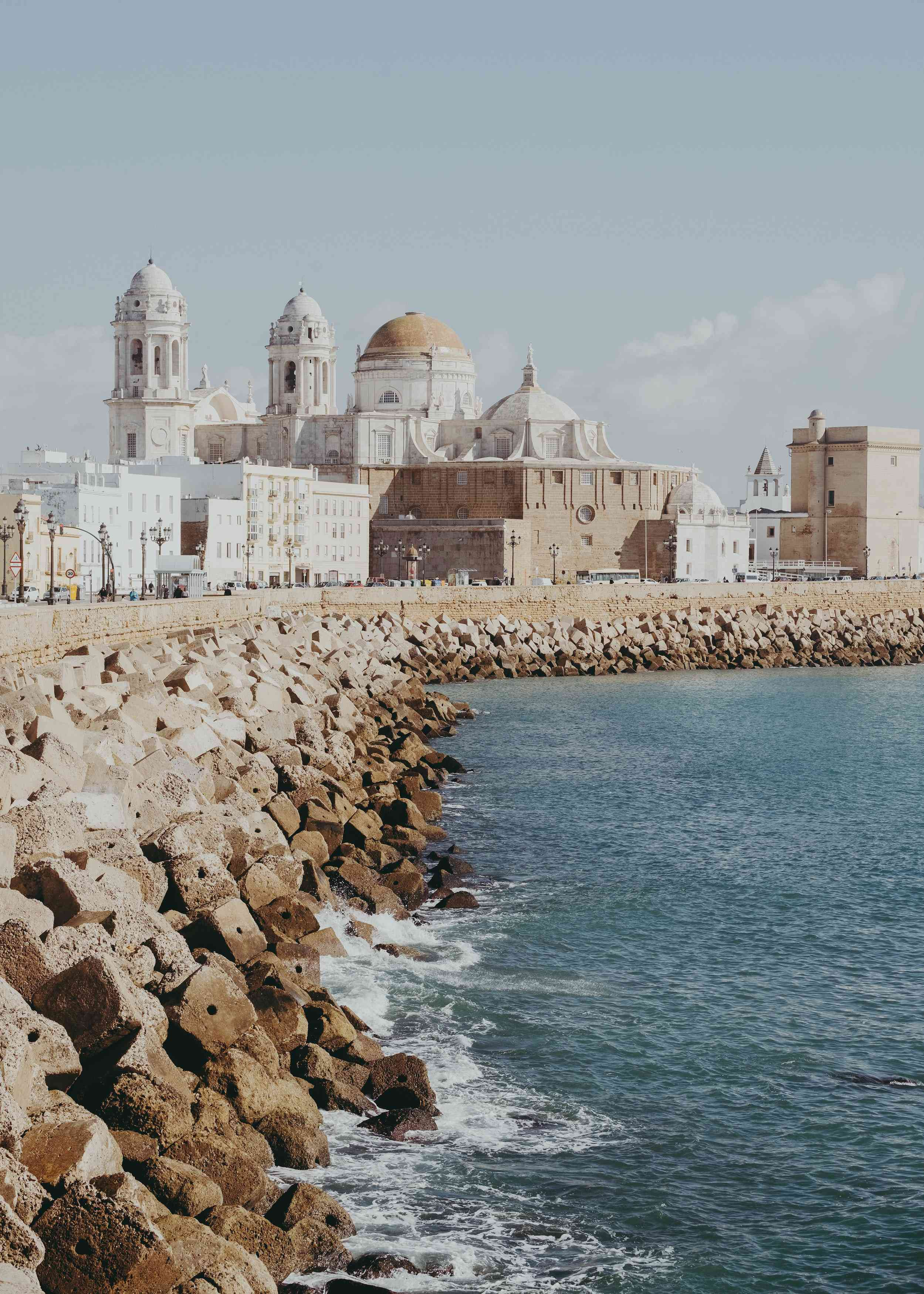 A rocky coastline leading up to a white palace in Cadiz, Spain