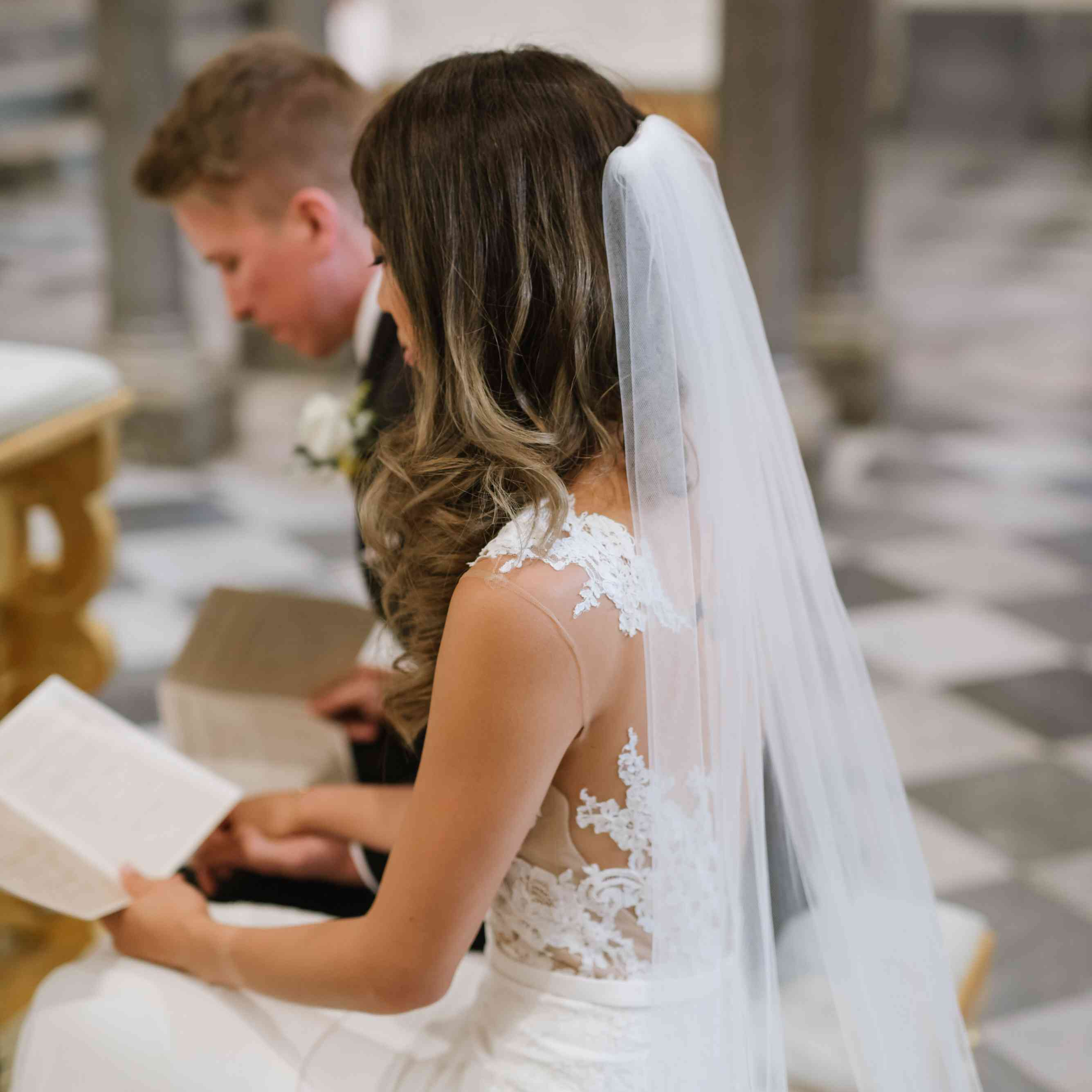 Bride reading pamphlet during ceremony