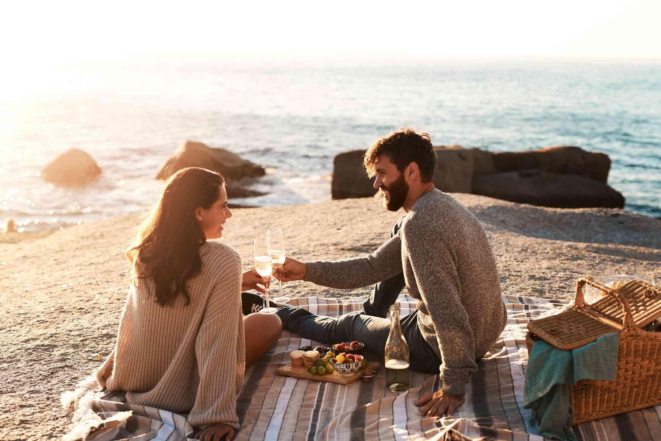 Couple enjoying picnic near ocean